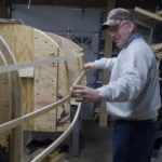 Andre Landry begins to apply cedar strips on what will be a 22-foot old style, square-sterned canoe taking shape in his garage.