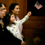 Scout Stradley, 5, of Rockport, waves an American flag as she watches her mom, Sarah Harvey, originally from England, be sworn in as an American citizen Friday morning at the Federal Building. U.S. Magistrate Judge John Nivison presided over the ceremony where 27 people from 21 different countries took the Oath of Allegiance.