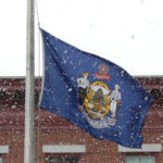 The Maine flag flaps as a snow squall moves through downtown Bangor on Sunday morning.