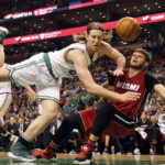 Boston's Kelly Olynyk (left) knocks over Miami's Tyler Johnson during the first half of Sunday's NBA game at TD Garden in Boston. The Celtics won 112-108 to earn a virtual first-place tie with Cleveland in the Eastern Conference.