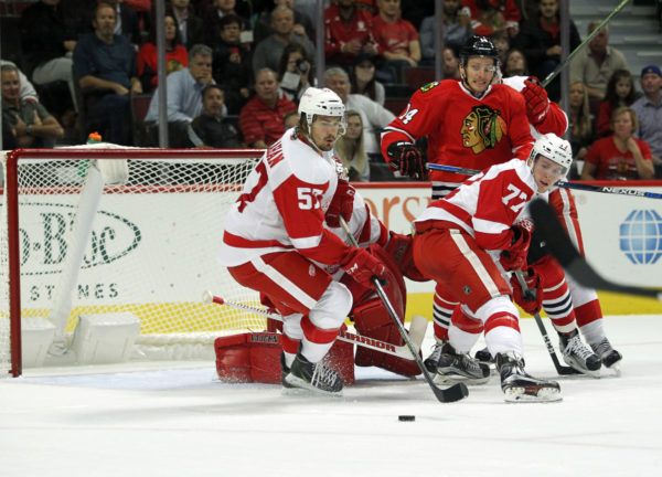 Detroit Red Wings defensemen Dan Renouf (77) and forward Mitch Callahan (57) go after the puck during the first period of play against Chicago Blackhawksduring a preseason game at United Center.