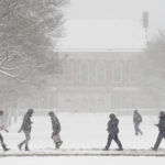 Students walk across the University of Maine through a 2017 spring snowstorm.