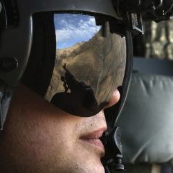 The Afghan mountains are reflected in the visor of a U.S. Army Airborne CH-47 Chinook window gunner while flying toward Forward Operating Base Gamberi, Dec. 7, 2014.