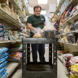 Ben Dionne stacks seeds on the shelves at Paris Farmers Union in Lewiston, where he works part-time. He was hired due to the help of vocational rehabilitation.