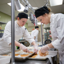 Eastern Maine Community College students Emily Kennedy (left) and Emily Howland pull baked cheese crisps off parchment paper in the kitchen of the Rangeley Cafe.