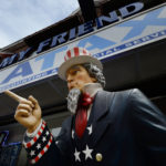 A tall statue representing Uncle Sam stands outside a tax preparation office in New York