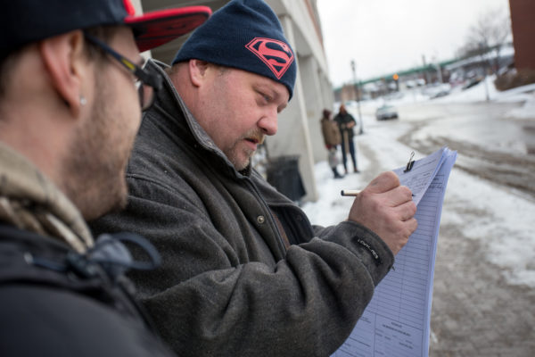 David McKenzie, 40, of Bangor signs a petition outside the garage at Pickering Square in Bangor, Jan. 13, 2016.
