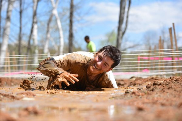 Aaron Sixberry, a student of the East Grand Outdoor Education Program, crawls through a mud pit as a part of the 2016 East Grand Adventure Race in Danforth.