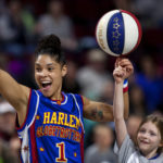 The Harlem Globetrotters' Ace Jackson (left) helps a young fan spin a basketball on her finger during their appearance at the Cross Insurance Center in Bangor on Thursday. Ashley L. Conti | BDN