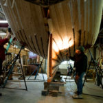 Volunteers Mae Boyle (left) and John Holliday seal seams on Black Jack, a friendship sloop, circa 1900, that they are helping restore at the Sail, Power and Steam Museum in Rockland. The restoration project has been going on for the past three years.