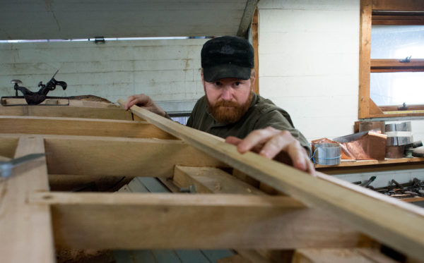 Shipwright Tim Clark works on fairing the deck frame of Black Jack, a friendship sloop that he and others at the Sail, Power and Steam Museum in Rockland have been restoring for the past three years.