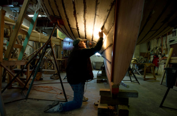 Volunteer John Holliday seals seams on Black Jack, a friendship sloop he and others at the Sail, Power and Steam Museum in Rockland have been restoring for the last three years.
