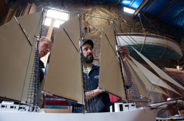 """Robert Guenther (left), volunteer, and Kirk Rouge, manager of the Sail, Power and Steam Museum in Rockland, look over the model of the """"Lavinia M. Snow,"""" a three-masted schooner built there in the late 1800s. Guenther built the model ship for the museum's sign after the original rotted."""