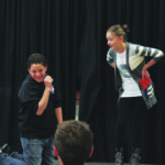 Antonio Vizcarrando (left) and Sarah Bartlett, Children's Theater Workshop participants, perform an improvised sketch for their peers.