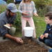 MCHT Farm Manager Aaron Englander (left) demonstrates how to plant garlic in the raised garden beds at Erickson Fields Preserve. Volunteer mentors will show families participating in Kids Can Grow how to recreate these raised beds at home.