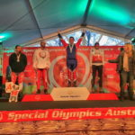 Lucas Houk (center) of Portland raises his arms to celebrate on Monday after being honored as the gold medalist in the Men's 5K Cross Country Freestyle event at the 2017 Special Olympics World Winter Games in Austria.