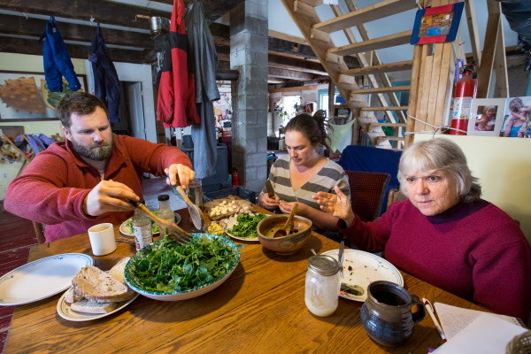 On a recent muddy, late winter day, Slow Money Maine coordinator Bonnie Rukin (right) sat down with the Mike and Christa Bahner on their farm over a lunch of fresh greens from their greenhouse and a medley of roasted vegetables that Rukin, a former organic farmer herself, brought.