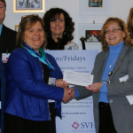 Delores Landry (left), house manager of Sarah's House, is presented with a check by Terri Vieira (right), president of Sebasticook Valley Health, during a ceremony at SVH in Pittsfield on February 22, 2017. In attendance included representatives of Sarah's House and employees of SVH who raised the funds to be donated.