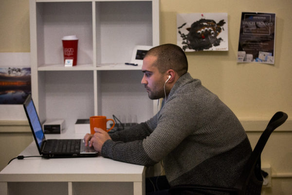 Ethan Evans works remotely from CoVort co-working space in Bangor on Friday for the Boston-based software development firm Appworks, supplementing a military career with the Maine National Guard and allowing him to buck a trend of the state losing its youngest workers in droves.
