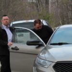 State Police Sgt. Christopher Tupper (left) places Jared Moody into his cruiser following the arrest.