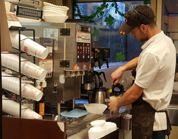 Odlin Road Dunkin' Donuts employee Lyndon Lydick pours a cup of coffee into a polystyrene foam cup for a customer on Tuesday.