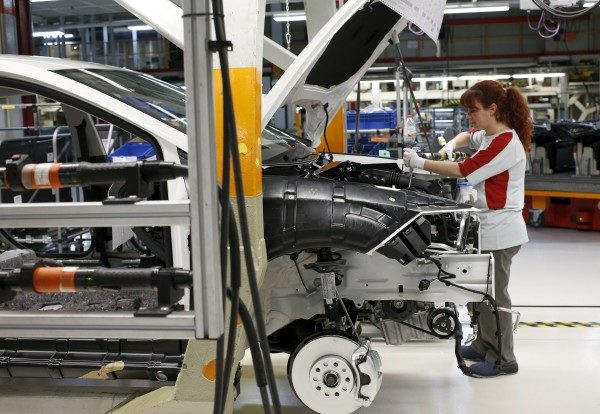 A worker from the SEAT factory, under the Volkswagen group, works on an engine of a SEAT Leon car, in Martorell near Barcelona December 5, 2014.  About 700,000 of the 11 million diesel engines involved in the Volkswagen emissions scandal were manufactured by the company's brand Seat, a spokesman for the Spanish unit said on Tuesday, September 29, 2015.  Picture taken December 5, 2014.     REUTERS/Gustau Nacarino