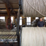 Bartlettyarns newest owner, Lindsey Rice, watches as the mill's old 1948 mule spins yarn.