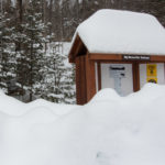 A snow pile covers half the kiosk at the trailhead for Big Moose Mountain on Feb. 12, near Greenville.