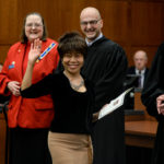 """Nongnud """"Nud"""" Simmons, 52, of Thailand, waves to her family and friends after she was sworn in as an American citizen at the Federal Building in Bangor. U.S. Magistrate Judge John Nivison presided over the naturalization ceremony where twenty-seven people from twenty-one different countries took the Oath of Allegiance."""