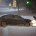 A person pushes their car out of a snow covered road in Bangor in March.