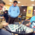 Nineteen-year-old Evan Viera [left] of Dover-Foxcroft studies the board at a meeting of the Queen City Chess Club while John Bapst Memorial High School physics teacher Michael Dudley [center] looks on. Organized by [right] Brian Hurst, 50, of Bangor, the club meets on Wednesdays at Books-a-Million in Bangor.
