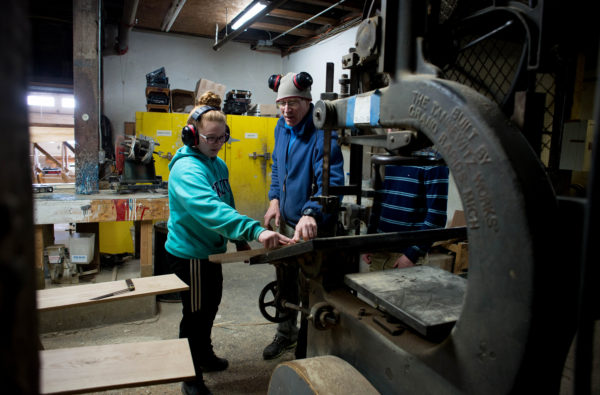 Payten Simmons (left) works with her instructor Terry Moore on a band saw at the Apprenticeshop (CQ) in Rockland during her fisherman's academy class. Six Oceanside High School students are participating in the school's program designed to keep young fishermen in school instead of dropping out without a high school diploma.