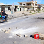 """Men ride a motorbike past a hazard sign at a site hit by an airstrike on Tuesday in the town of Khan Sheikhoun in rebel-held Idlib, Syria April 5, 2017. The hazard sign reads, """"Danger, unexploded ammunition."""""""