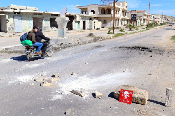Men ride a motorbike past a hazard sign at a site hit by an airstrike on Tuesday in the town of Khan Sheikhoun in rebel-held Idlib, Syria April 5, 2017. The hazard sign reads, &quotDanger, unexploded ammunition.&quot