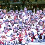 The Denver Pioneers and head coach Jim Montgomery (lower left) celebrate their 3-2 win over the Minnesota-Duluth Pioneers in the national championship at the Frozen Four at the United Center in Chicago on Saturday night.