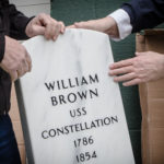 Larry Glatz (left) and Herb Adams unwrap William Brown's gravestone for the first time. It was 160 years in coming.