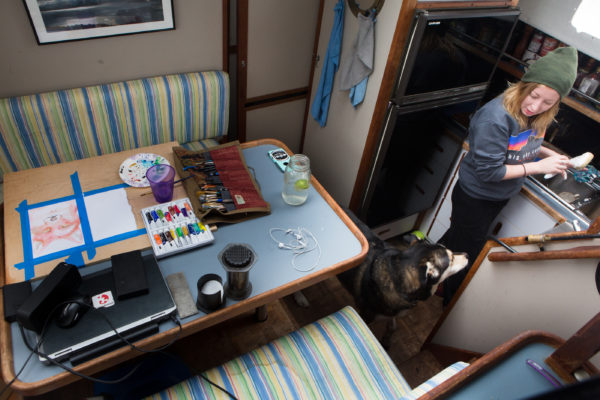 Krystin Noyes washes dishes below decks while her dog, Cirroc, watches in Portland. Noyes spent the winter on the 36-foot boat on at Dimillo's Marina with the dog, a cat and her boyfriend, Nate Taylor.