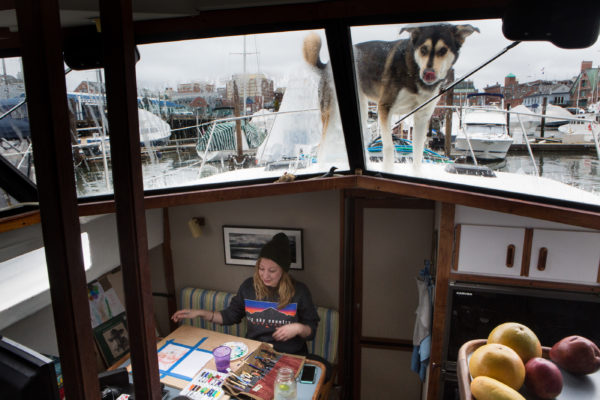 Krystin Noyes works on a watercolor paining below decks while her dog, Cirroc, roams around outside in Portland. Noyes spent the winter on the 36-foot boat at Dimillo's Marina with the dog, a cat and her boyfriend, Nate Taylor.