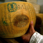 An Italian grocer shows off his Parmesan cheese inside a shop in central Rome, May 20, 2003.