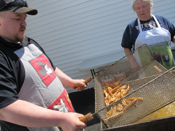 Evan Emerson pulls freshly cooked smelt out of the fryer at the Columbia Falls Smelt Fry on April 15, as fellow cooker Muriel Gay looks on.