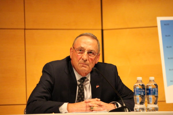 Gov. Paul LePage looks on as protesters chant during a student-organized town hall at the University of Southern Maine's Portland campus.