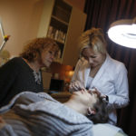 An aesthetician shapes the eyebrows of a client