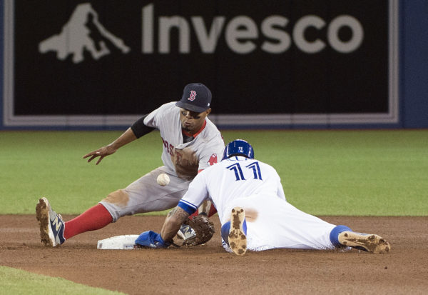 Toronto Blue Jays center fielder Kevin Pillar (11) slides safe into second base ahead of the tag by Boston Red Sox shortstop Xander Bogaerts (2) in the seventh inning during Wednesday night's game at Rogers Centre in Toronto.
