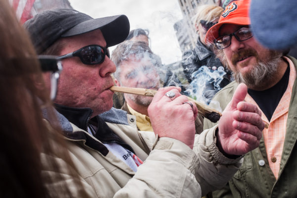 Robert Chute (right) and a man who only gave his name as Michael L. light up a large joint in Portland's Monument Square on Thursday afternoon, 4/20. The weed was a gift to the crowd from legalization activist Crash Barry who also handed out free copies of his latest book &quotMarijuana Valley.&quot