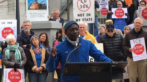 Portland City Councilor Pious Ali speaks at a rally in Augusta on Thursday.