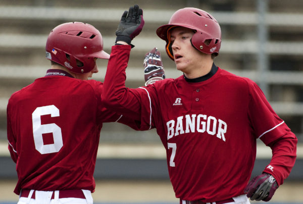 Bangor's George Payne (right) celebrates with teammate Tyler Parks after scoring a run against Lewiston during their baseball game at Mansfield Stadium in Bangor Friday.