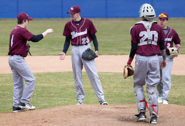 Mattanawcook Academy's Cameron Fournier (center) talks with his teammates before an inning against Katahdin during their baseball scrimmage at Mansfield Stadium in Bangor Tuesday.