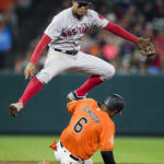 Boston shortstop Xander Bogaerts jumps over Baltimore's Jonathan Schoop while turning a double play to end the eighth inning during Saturday night's game at Oriole Park at Camden Yards. The Orioles defeated the Red Sox 4-2.