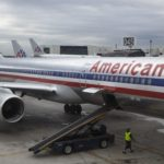 A worker walks underneath an American Airlines airplane at Miami International airport in Miami, Nov. 29, 2011.