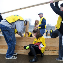 Cameron Croft (left), 14, and Donna Reitze (right), 17, move slabs of wood while Brian Fortie (second from left) holds a board so Alanna Thomas, 14, can screw it to the support to construct a raised garden bed for the Maple Street Community Garden in Brewer Saturday.